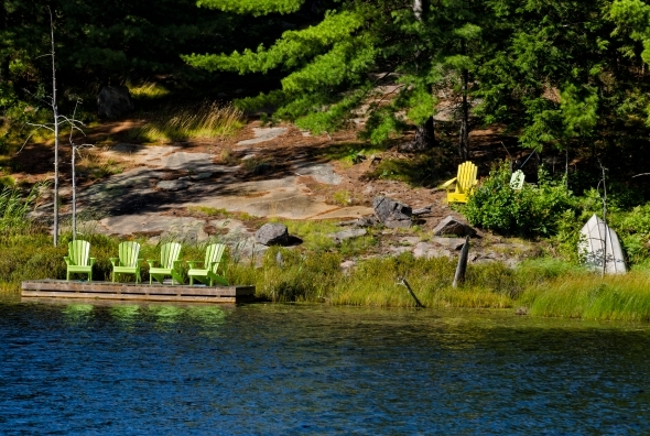 Green Adirondack chairs on a dock