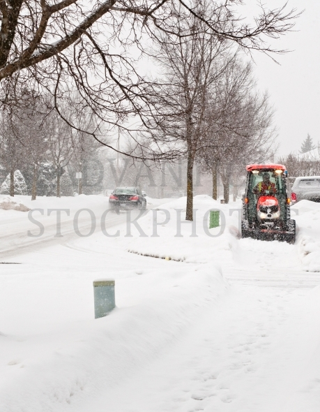 Clearing snow from sidewalk on suburban street