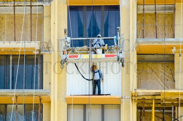 Construction workers repairing balconies