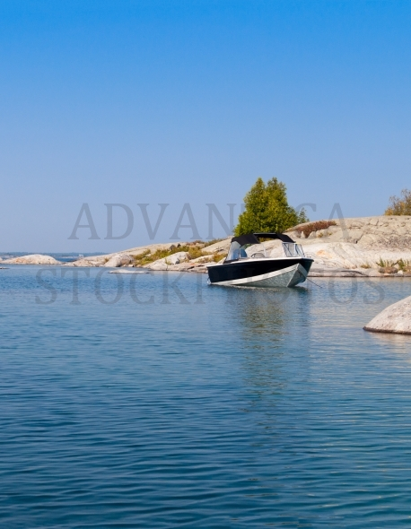 Power boat on a blue lake at a rocky island