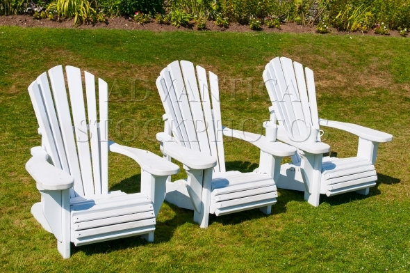 Three white Muskoka chairs on a lawn