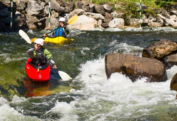 Two kayak paddlers on a whitewater slalom course