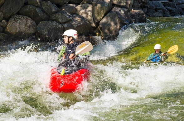 Two female kayakers on a whitewater river