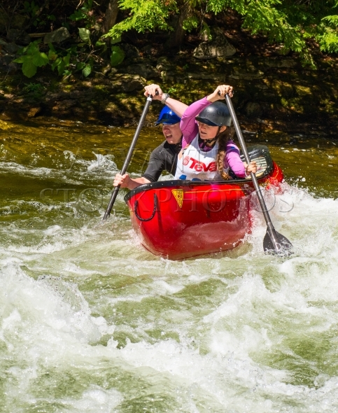 Mixed team in a tandem whitewater canoe