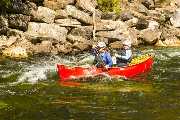 Two women paddling a tandem whitewater canoe