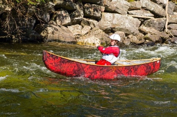 Young woman paddling a whitewater canoe