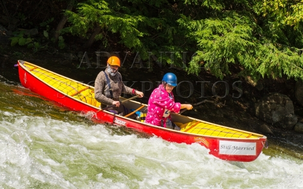 Married couple paddling in whitewater canoe