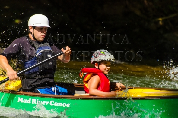 Father and son paddling green whitewater canoe