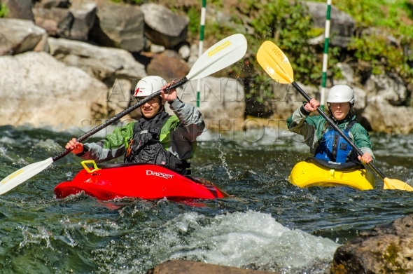 Two girls running rapids in whitewater kayak