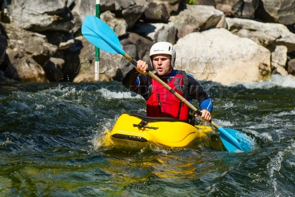 Male paddler in a kayak on a whitewater course