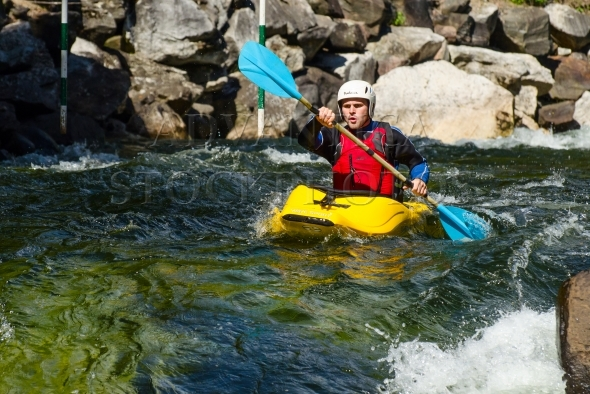 Young man in a yellow whitewater kayak