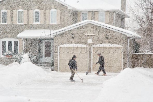 Two men clearing driveway in a snowstorm