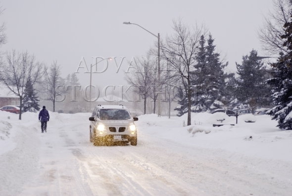 Car and a pedestrian on a snowy road in winter