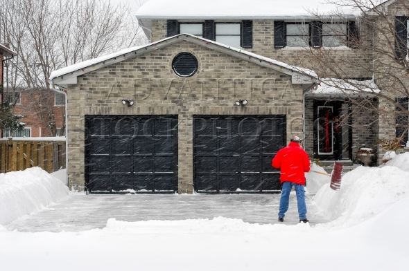 Man clearing driveway in winter during snowstorm