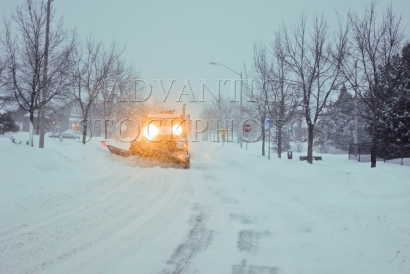 Snowplow truck in winter on a suburban street