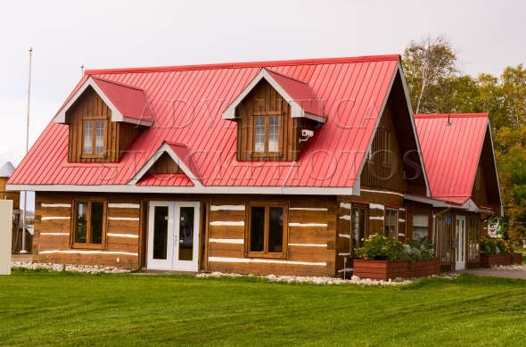 Contemporary log building with red metal roof
