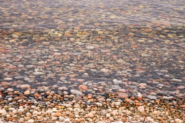 Colorful pebbles on the beach and under water