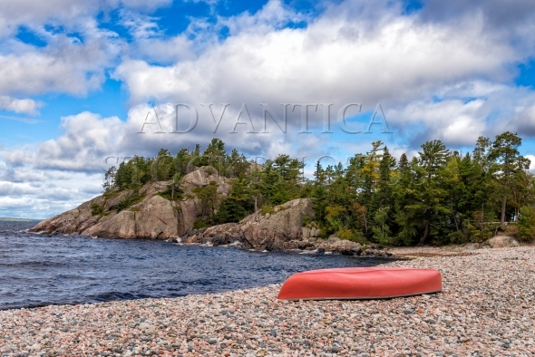 Red canoe on a pebble beach in sheltered cove