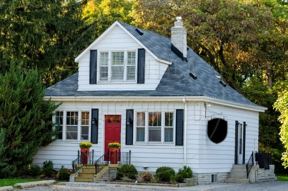 Pretty house with red door under tall trees