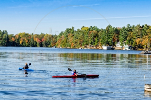 Two kayaks on a calm lake in the fall