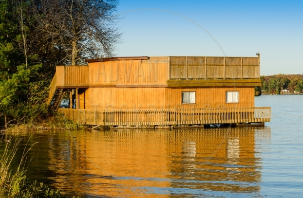 Wooden boathouse with reflection in the water