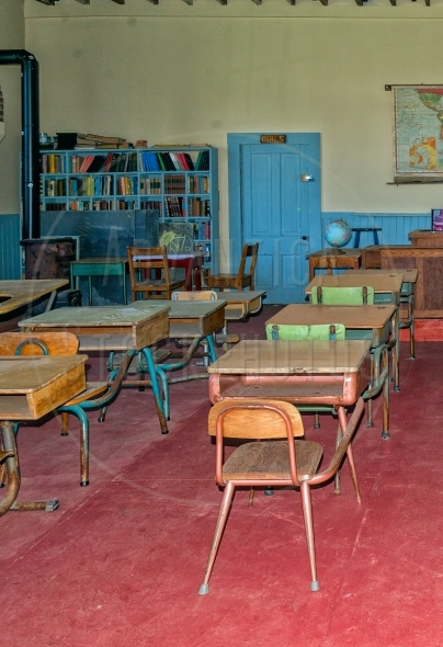 Old classroom with bookshelf and pupil desks