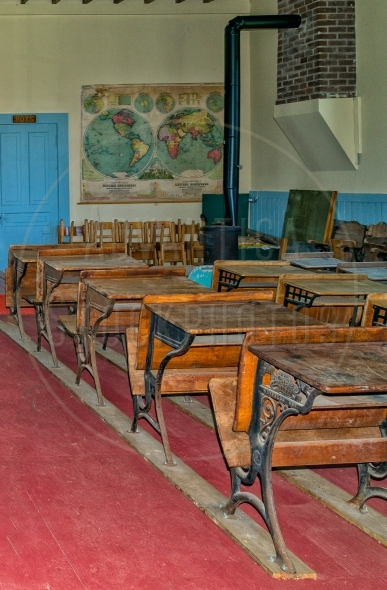 Old classroom with a worldmap and pupil desks