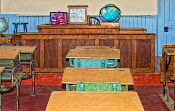 Old classroom with a podium and pupil desks