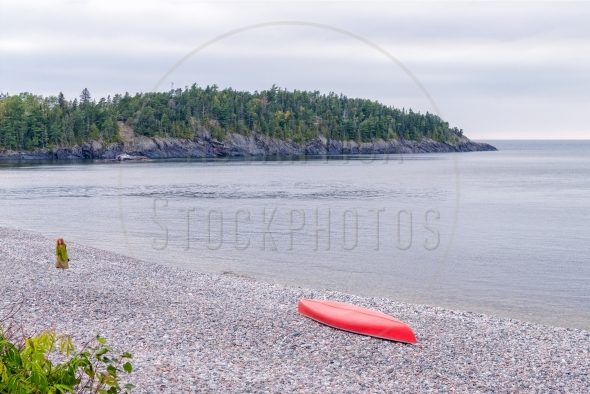 Red canoe and a woman on a pebble beach