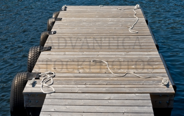 Wooden Dock image with tire bumpers and ropes