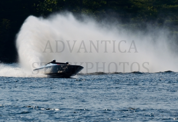 Fast power boat leaving a tall spray wall