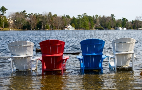 Colored chairs on a flooded dock