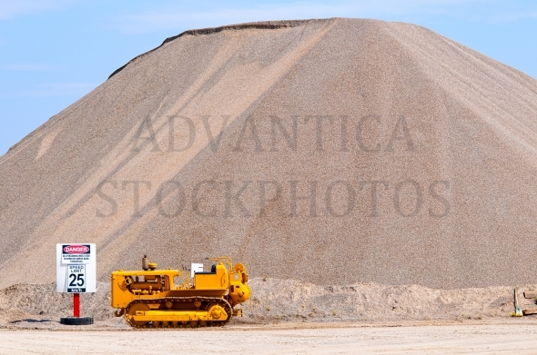 Small bulldozer at a large sand hill
